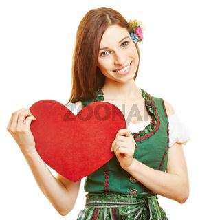 Frau im Dirndl trägt rotes Herz