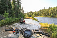 People driving ATV quads through water. Lake in Ontario, Canada.