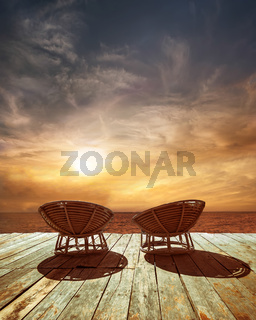 Sunset at tropical ocean beach with chairs for relaxation on wooden terrace