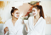 Happy girls in bathrobes with masks