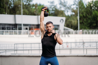 Sportive guy training with kettlebell. Strength and motivation.