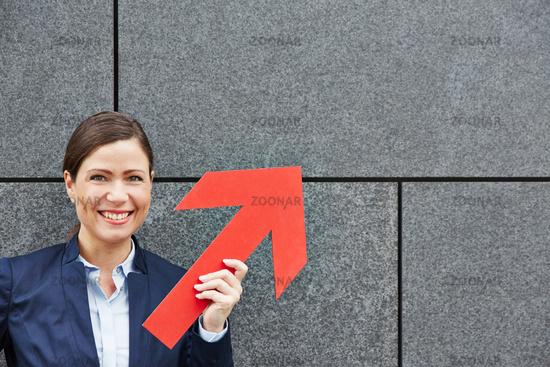 Geschäftsfrau hält roten Pfeil nach oben