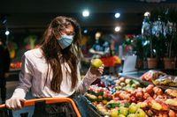 The girl with surgical mask is going to buy apples.