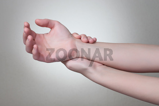 A young woman touching her painful wrist