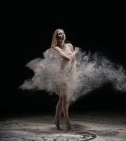 Barefoot woman dancing nude in cloud of dust