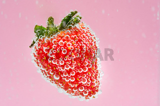 Red strawberry fruit floating in the water on pink background. High value commercial food photography. Fresh beverage drink concept.