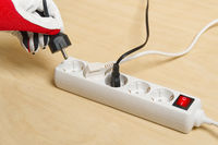 Closeup of an electrician plugging extension cords into each other. Mans hand plugging extension cord