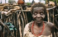 TOPOSA TRIBE, SOUTH SUDAN - MARCH 12, 2020: Old blind woman from Toposa Tribe standing on blurred background of stick hut in village in South Sudan, Africa