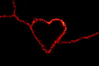 Red electric discharge in the form of a heart on a black background. Greeting card for valentines day. Bright light effect. The concept of relationships and love.
