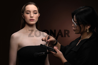 Beauty makeup artist working on a fashion model pretty face isolated on black background. Beautiful model at make up artist. Make-up artist, applying eye shadow to the model