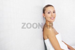 Lächelnde Frau sitzt im Bad an Fliesen