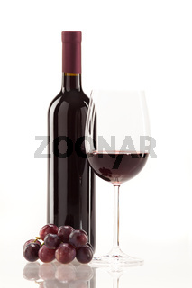 Red wine in glass with fruit, leaves and wine bottle