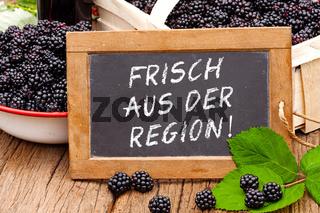 Tafel mit Text: Frisch aus der Region vor Brombeeren