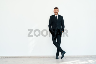 Smiling confident businessman in elegant suite posing on white wall background