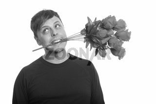 Studio shot of crazy Caucasian man biting roses and thinking ready for Valentine's day