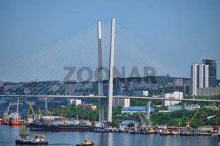 Vladivostok, Russia - Jun 11, 2020: Evening view of the bridge in the Golden swarm Bay. Sea city beach in summer.