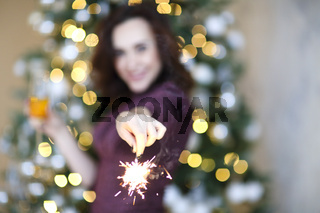 Happy woman with sparkler and champagne against Christmas tree