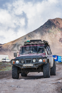 Japanese sport utility vehicle Nissan Patrol driving on mountain road on background volcano landscape. Off-road trip in volcanic travel destinations