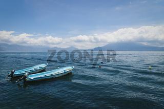 Two blue boats on lake Atitlan with view on volcanoe in Santa Cruz la Laguna, Guatemala