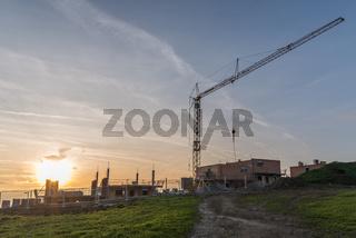 Baukran auf einer Baustelle bei stimmungsvollem Sonnenuntergang