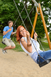 Laughing teenage couple on swing in park