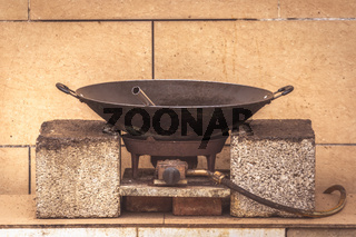 Old black metal pan wok on a gas cooker