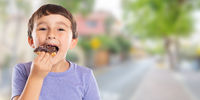Little boy child eating donut town banner copyspace unhealthy sweet sweets