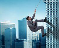 Businessman in challenge concept climbing skyscraper