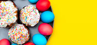 Colored painted eggs on a yellow background. Easter banner. Festive banner with place for text. Religious holiday.