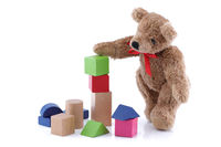 Cute teddy bear playing with toy wood blocks