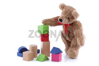 Cute teddy bear playing with toy wood blocks