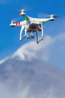 Flying UAV drone quadcopter aerial videography in sky on background volcano eruption
