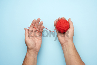 two male hands hold a ball of red woolen threads, blue background