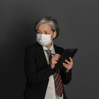 Masked Caucasian businesswoman writes with pen in blank while looking at side. Quarantine concept