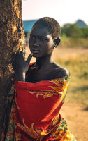 BOYA TRIBE, SOUTH SUDAN - MARCH 10, 2020: Young woman in colorful garment touching lip and looking away while leaning on savanna tree trunk near Boya Tribe village in South Sudan, Africa