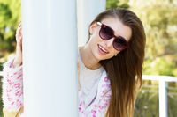 Close up young woman hiding behind a column in a park portrait