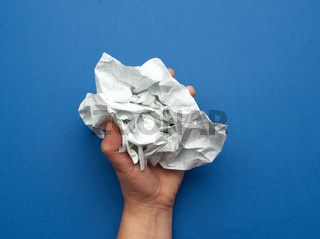 woman holds in her hand a crumpled sheet of paper