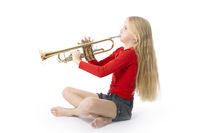 young girl in red playing trumpet