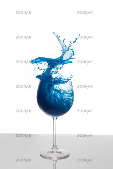 Blue liquid splashing out of a glass