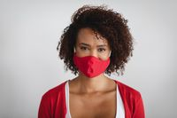 Portrait of african american woman wearing face mask against grey background