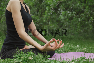Woman doing yoga in lotus position sitting on grass