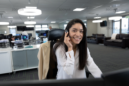 Portrait of businesswoman using headset at modern office