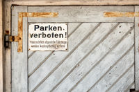 private no parking sign with german text Illegally parked vehicles will be towed at the owner's expense