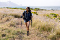 Fit african american woman wearing backpack nordic walking on coast