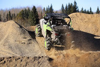 A side-by-side ripping up dirt as it goes up a gravel hill
