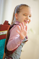 Mädchen mit Schulranzen geht zur Schule
