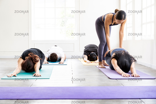 Asian Yoga coach tarining to yoga student