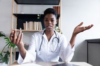 Mixed race female doctor sitting having a video chat going through paperwork