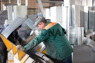Belarus, Gomel, 25 April 2018. Factory for the manufacture of ventilation pipes.Two workers make metal ventilation pipes in the workshop at the factory