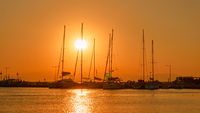 Silhouettes of yachts with tall masts at sundown